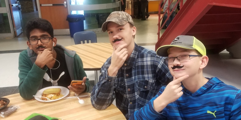 Sporting mustaches in support of Movember, bringing awareness to men's health issues.